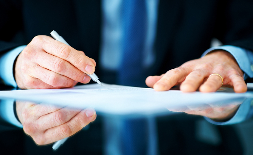 Business man hand signing on document at desk